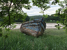 Rusting boat sitting on grass and backround water